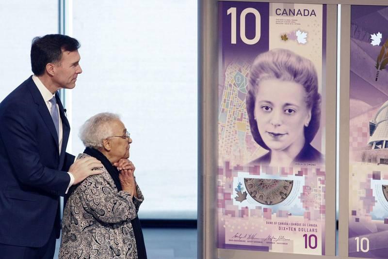 viola desmond looking at a large $10.00 bill.