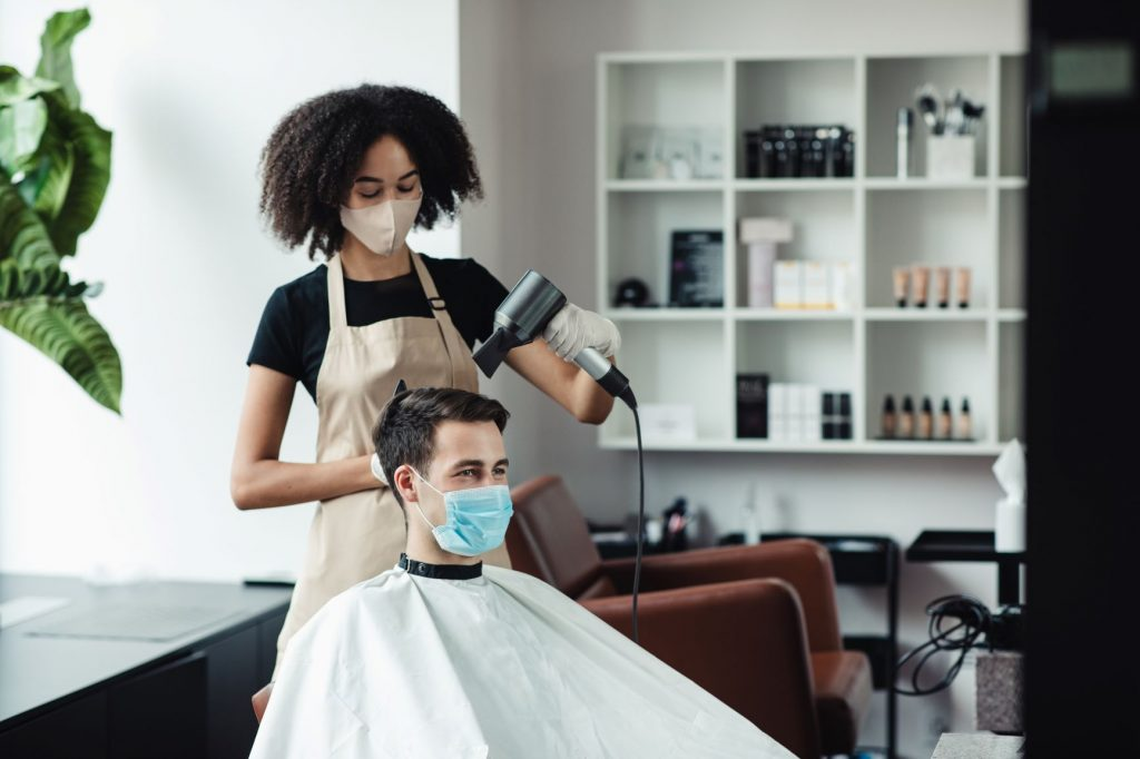 woman using hair dryer on man
