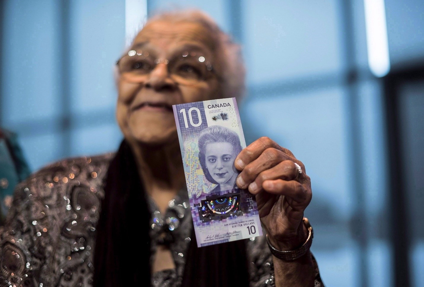 viola desmond holding $10.00 bill.