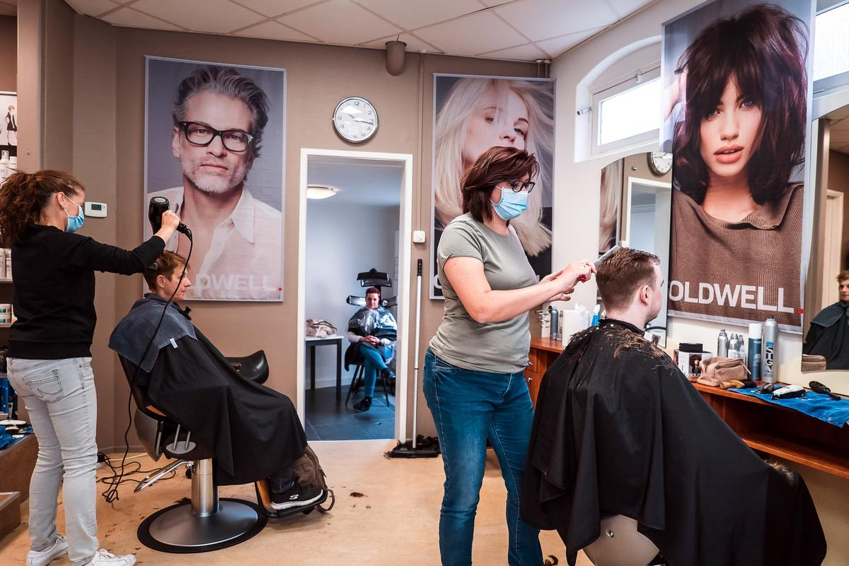 people getting hair cuts in a salon